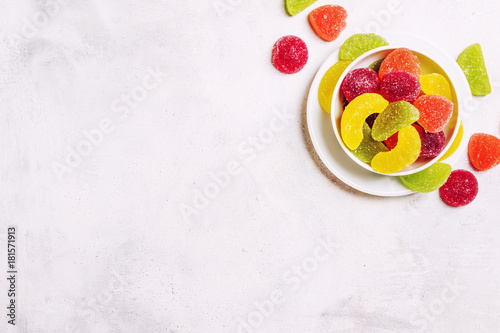 Multicolored jelly marmalade in sugar, gray background, top view