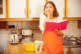 Housewife with cookbook in kitchen. - 181577730