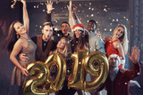 New 2019 Year is coming! Group of cheerful young multiethnic people in Santa hats carrying gold colored numbers and throwing confetti on the party - 181588152