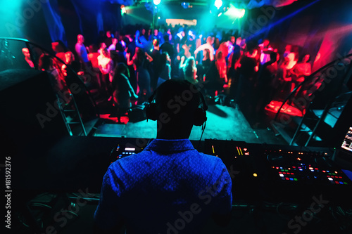 silhouette of DJ playing music on mixer and a lot of people dancing in nightclub on stage