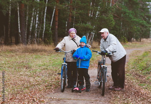Poster grandparents on bikes with grandson on schooter ride in nature