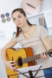young woman holding guitar and learning to play song - 181595180