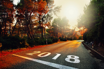 New Year 2018 number painted on colorful sunset asphalt road. © robsonphoto