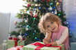 Girl playing in the room with a Christmas tree
