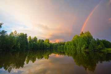 Rainbow over calm water of a forest lake. Beautiful clouds in the evening sky.