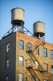 Classic view of old New York City water towers atop old brick buildings with external fire escapes - 181604984