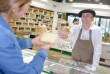 Man in French atire passing cheese to customer - 181608170