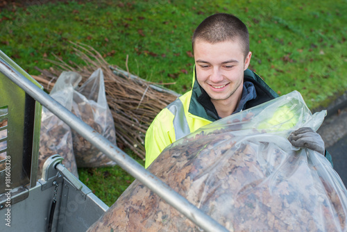 young worker loading bag of dead leaves into vehicle