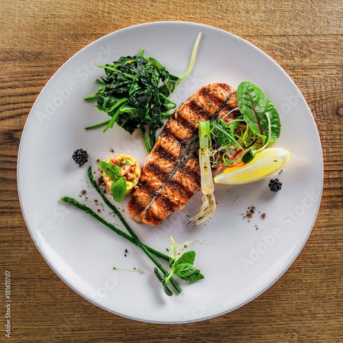 Salmon fish stake cooked on a grill with healthy salad on a plate. Healthy food made of fish and vegetables on a table. Top view. - 181611707