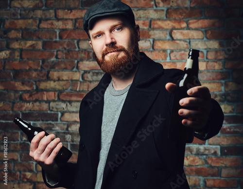 A man holds beer bottle. Poster