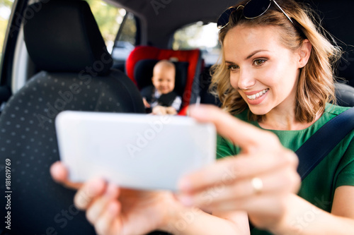 Young mother with smartphone and baby boy in the car.