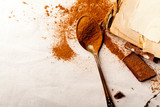 Tea spoon with spilled cocoa powder on linen background with old-fashioned cookbooks aside. Top view. Vintage kitchen concept. Horizontal composition with copy space. - 181624948