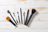 Lineup of artist makeup accessories with eyeshadow and blush brushes - 181627585