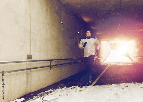Fotobehang Hardlopen happy man running along subway tunnel in winter