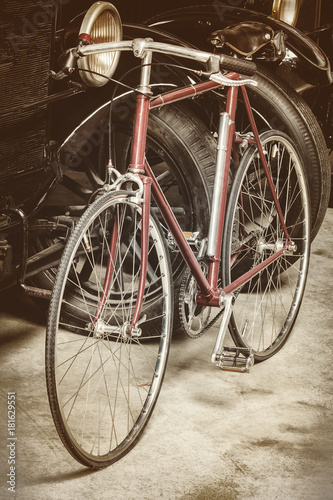 Fotobehang Fiets Ancient rusted racing bicycle and black cars