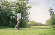 Man playing golf on a golf course in the sun.Golfer hitting golf shot with club on course .