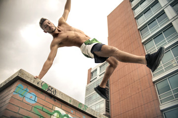 Athletic guy jumping down from a building