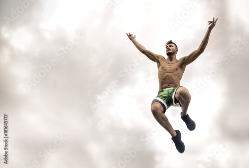 Póster Sportive guy jumping high in the sky