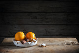 christmas cookies and oranges in a bowl on a rustic table, dark wooden background with a large copy space, moody light - 181647508