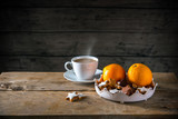 Christmas cookies and oranges in a bowl and a cup with hot coffee on a rustic table, dark wooden background with a large copy space, moody light - 181647988