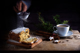 christmas cake, in germany christstollen, hand sprinkling powdered sugar, coffee cup, spices and cinnamon star cookies on a rustic wooden table, dark background, copy space, selected focus - 181648195