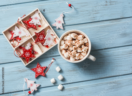 Tuinposter Chocolade Hot chocolate with marshmallows and cinnamon, christmas decorations on a blue wooden background. Christmas background. Free space, top view, flat lay