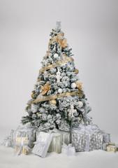 In Weiß, Gold und Silber geschmückter verschneiter Christbaum mit schön verpackten Geschenken