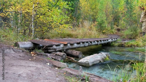 mata magnetyczna Tourist man crossing small wooden boardwalk bridge over forest creek in Altai mountains in rainy Autumn day