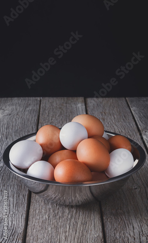 Fresh brown eggs in bowl on wood at black background