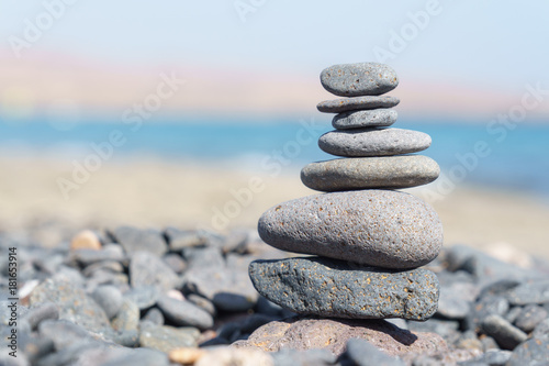 Foto op Plexiglas Stenen in het Zand Close-up of stack of stones in perfect balance on a tranquil sunny beach in Fuerteventura, SpainClose-up of stack of stones in perfect balance on a tranquil sunny beach in Fuerteventura, Spain