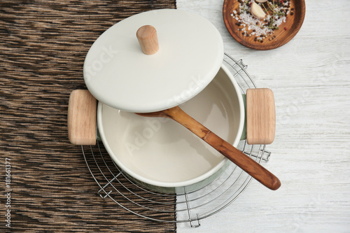 Fotobehang Kruiden 2 Stewpan with lid and wooden spoon on table