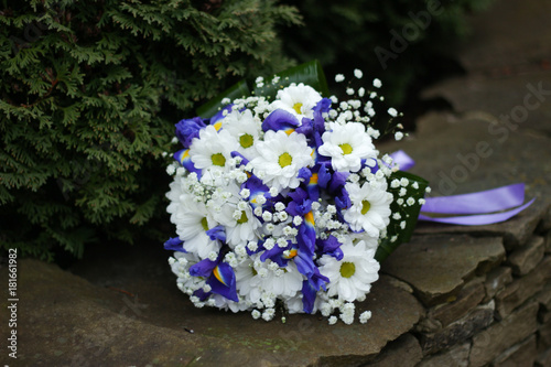 Plexiglas Iris bouquet with daisies and irises on a green background