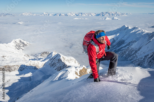 Staande foto Bleke violet Mountaineer climbing up a snowy ridge in the alps