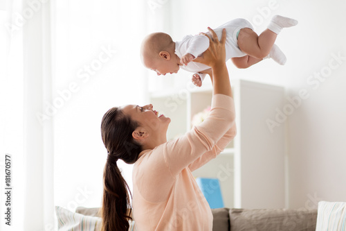 happy mother playing with little baby boy at home