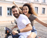 Cheerful young couple riding a scooter and having fun - 181672519