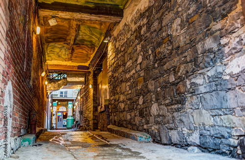 Tuinposter Smal steegje Old town street narrow dark brick alleyway or alley with path