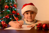 A letter to Santa Claus concept. Cute little girl with a pen at the table by the Christmas tree - 181679328