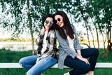 Two pretty brunette girls talking outdoor in the park - 181690735