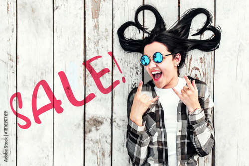 Brunette girl on wooden background with ''sale'' word on it