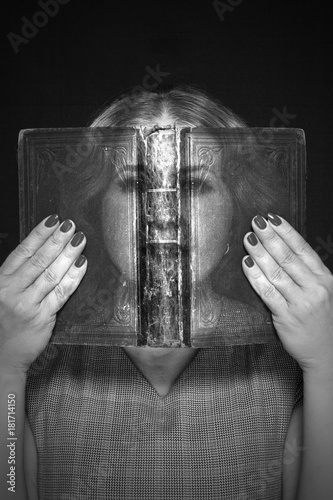 A woman looks through a book Poster