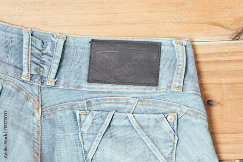 Female blue torn jeans shorts on old wooden background Poster