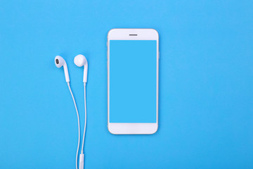 Top view mockup smartphone and earphones on blue pastel background
