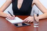 Female hand writes a pen in a notebook, on the Desk next to a smartphone and a glass of water - 181738154