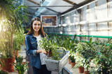Portrait of young female shopper walking through indoor garden store looking at camera smiling. - 181739952