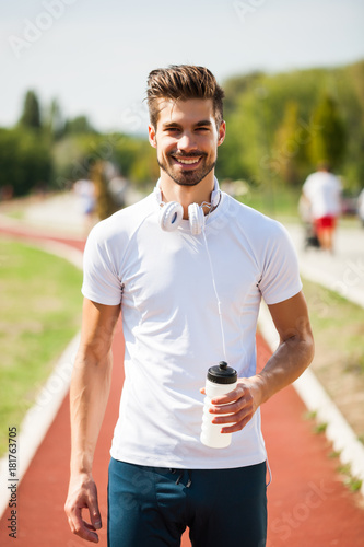 Foto op Plexiglas Jogging Young man is drinking water after jogging on sunny day.