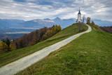 Jamnik, Slovenia - The beautiful church of St. Primoz in Slovenia near Jamnik with beautiful clouds and Julian Alps at background - 181764170
