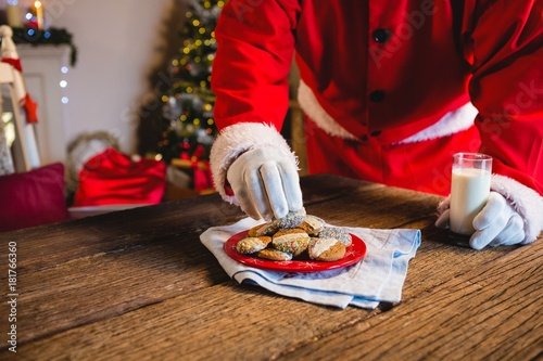 Santa Claus selecting a cookie with glass of milk