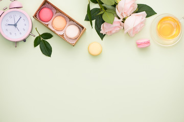 Colorful macaroons and rose flowers with gift box on wooden table. Sweet macarons in gift box. Top view