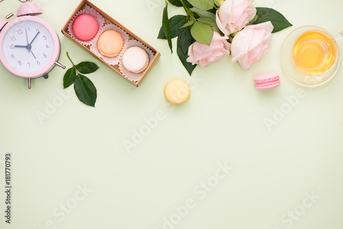 Foto op Aluminium Macarons Colorful macaroons and rose flowers with gift box on wooden table. Sweet macarons in gift box. Top view