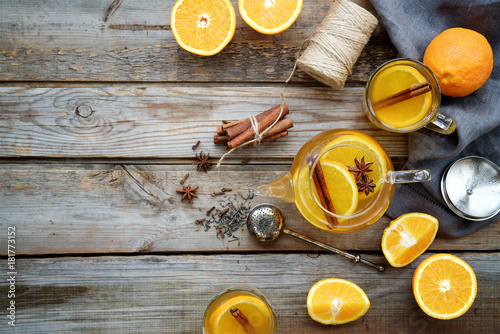 Fototapeta Hot orange tea with spices on wooden rustic background